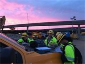 Construction workers gather near highway