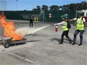 CERT trainee using a fire extinguisher