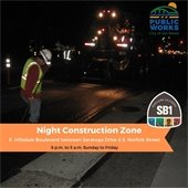 construction workers on a road at night
