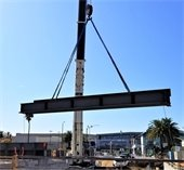 A crane lifting a metal beam for a new grade separation