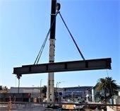 A crane lifting a metal beam for a new grade separation