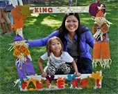 A mom and child on the grass at fall festival