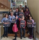 Library staff holding posters on staircase