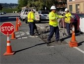 Public works crews repair a road