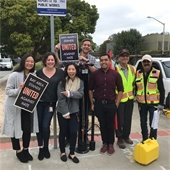 Public Works staff outside holding a poster