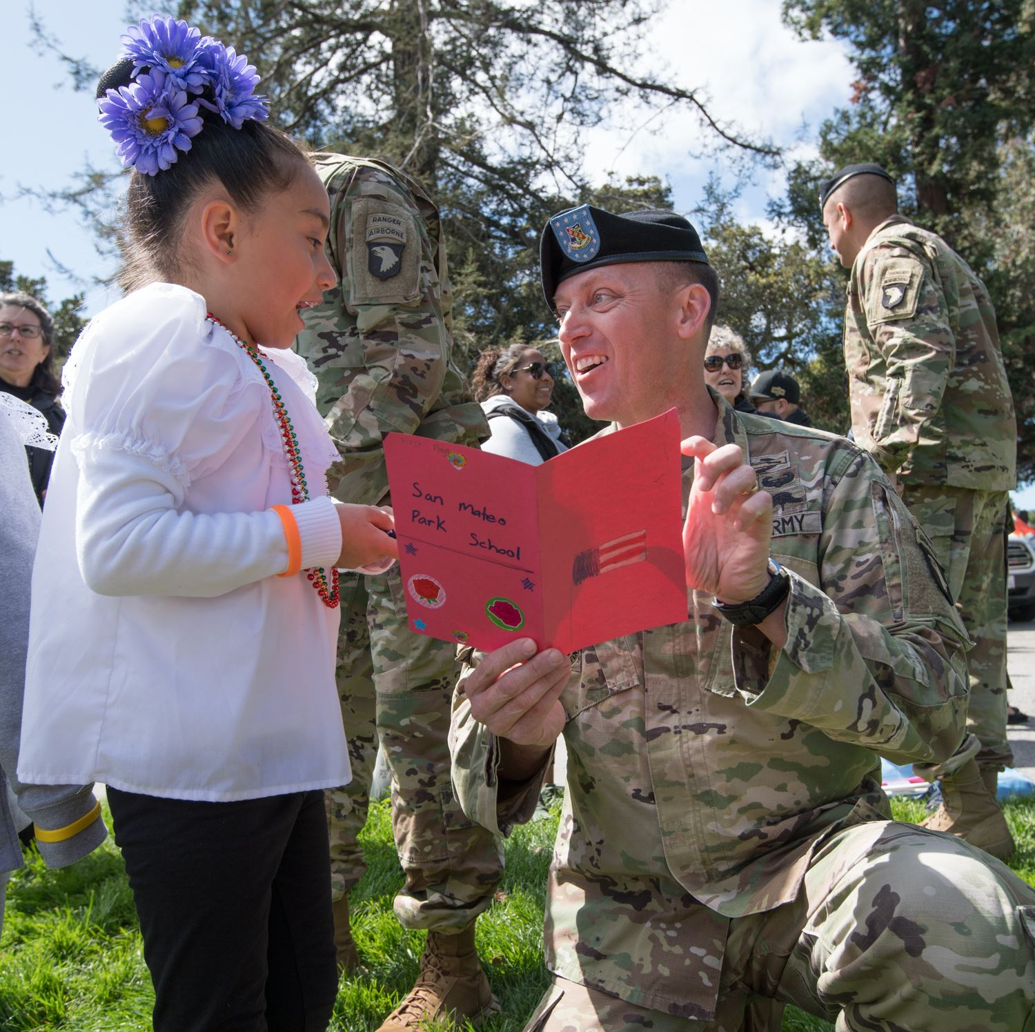 Girl gives soldier a card photo