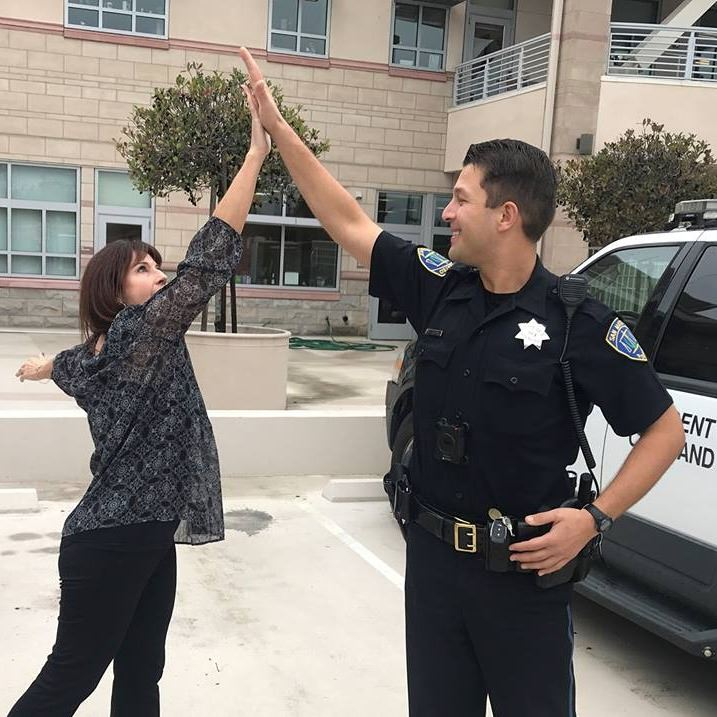 Police officer giving high five to community member.