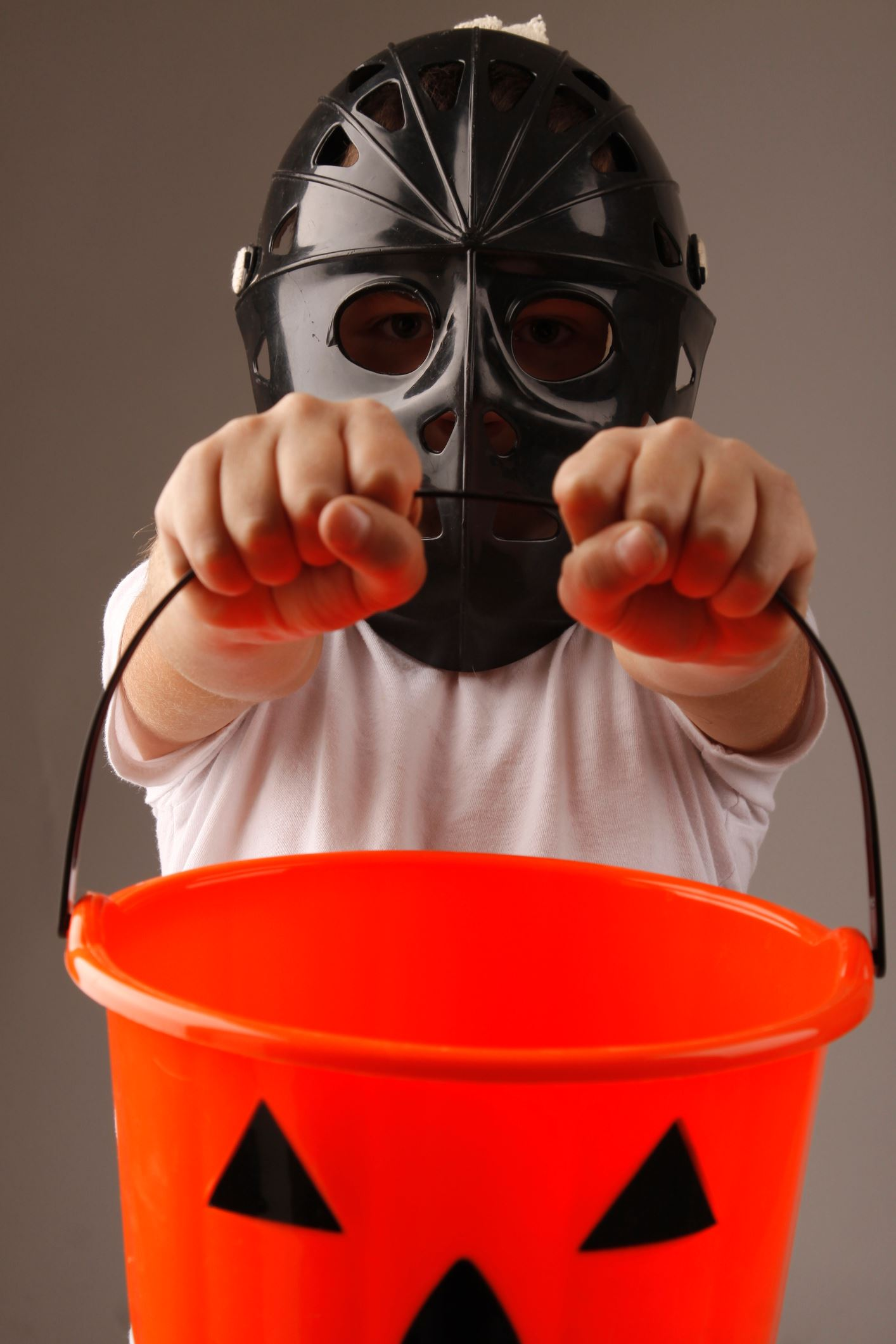 Photo of child dressed in a Halloween costume holding bucket for candy.